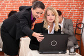 Two co-worker in restaurant looking at laptop screen — Stock Photo