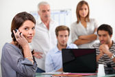 Young woman on the phone with colleagues gathered round a laptop — Stock Photo