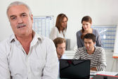 55 years old man watching us and four young focused on a laptop — Stock Photo
