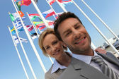 Businessman and woman with flags. — Stock Photo
