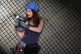 Girl with drill on squared background — Stock Photo
