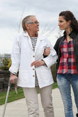 Young woman helping elderly person to walk with a crutch — Stock Photo