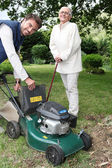 Senior with gardener and lawnmower — Stock Photo