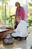 Young woman vacuuming for an elderly lady — Stock Photo