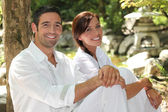 Couple in white in a oriental stone garden — Stock Photo