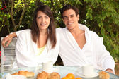 Young couple having breakfast outside — Stock Photo