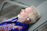 Man laying on deck chair listening to music — Stock Photo