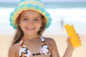Little girl on the beach with a sun cream — Stock Photo