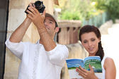 Couple of tourists with camera and guide book — Stock Photo