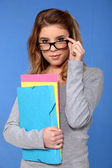 Female student holding files against blue background — Stock Photo