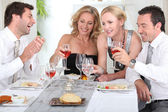 Four joyful at the start of a posh dinner. — Stock Photo
