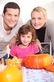 Young family carving pumpkins — Stock Photo