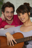 Girlfriend playing the guitar for her boyfriend — Stock Photo