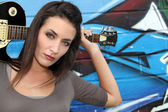 Female guitarist standing in front of a graffitied wall — Stock Photo