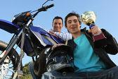 Hombre parado con motos y trofeo — Foto de Stock