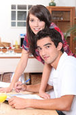 Young couple doing paperwork at the kitchen table — Stock Photo