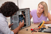 Man repairing computer under his wife's — Stock Photo