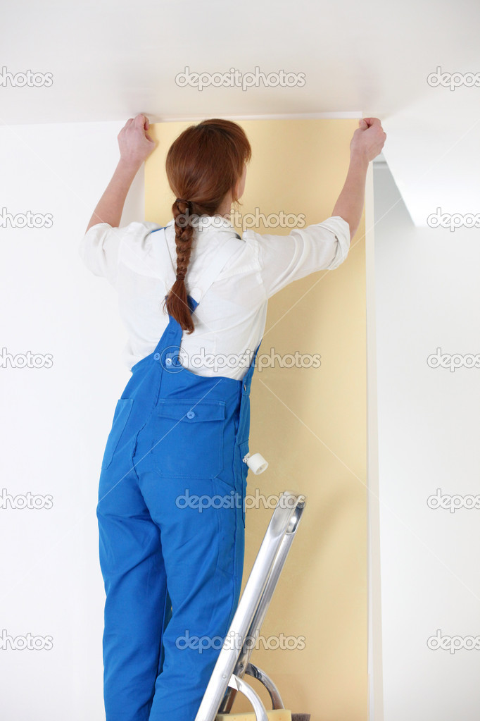Woman putting up yellow wallpaper — Stock Photo #7673001
