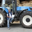 Stockfoto: Farmer using a laptop on his tractor