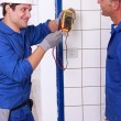 Two young plumbers larking about with a voltmeter - Stock Photo