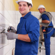 Electricians working in a tiled room -  