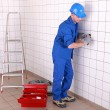 Electrician wiring a large tiled room - Stockfoto