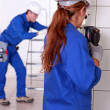 Stock Photo: Female electrician drilling a wall