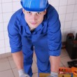 Royalty-Free Stock Photo: Plumber preparing to cut piece of pipe