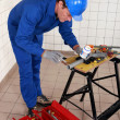 Stock Photo: Experienced plumber at work with miscellaneous tools