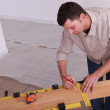 Man measuring plank of laminate flooring — Stock Photo #7699178
