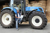 Farmer using a laptop on his tractor — Foto Stock