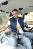 Farmer in the cab of his tractor — Stock Photo