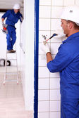 An electrician screwing an electrical outlet and a colleague on a stepladde — Foto de Stock
