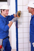 Two young plumbers larking about with a voltmeter — Stock Photo