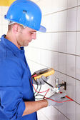 Plumber checking wiring with a voltmeter — Stock Photo