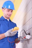 Electrician is checking an outlet with an ammeter — Stock Photo