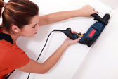 Handywoman drilling a hole in the ceiling — Stock Photo