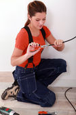 Handywoman using stripping pliers on a wire — Stock Photo