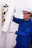 Man inspecting fuse box — Stock Photo