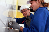A young female electrician and a mature electrician — Stock Photo