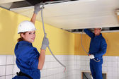 Young female electrician with mentor — Stock Photo