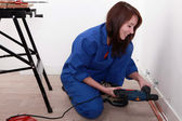 Female labourer drilling hole in wall — Stock Photo