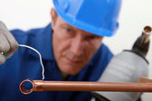 Skilled tradesman in blue jumpsuite is soldering a copper pipe — Zdjęcie stockowe