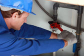 человек, используя большой красный ключ на некоторых внутренних водопроводных труб — Стоковое фото