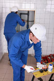 Plumber marking and cutting pipe — Stock Photo