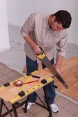 Handyman cutting a board — Stock Photo