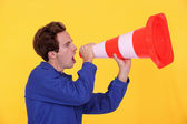 Young blue collar shouting in construction cone — Stock Photo