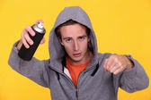 Hooded youth with paint can — Stock Photo