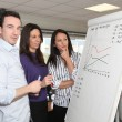 Stock Photo: Sales team standing at a flipchart