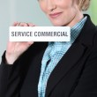 A young businesswoman looking at us with a sign in her hand. — Stock Photo